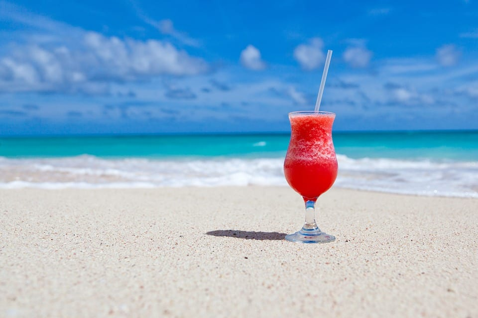 A cocktail rests on the white sand of an exotic beach.